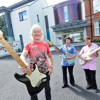 Brian Bennett with Patricia McCabe (right), Nursing Auxiliary, NI Hospice and Charmain Geehan, Nursing Auxiliary, NI Hospice, with some of the 19 Fender Statocaster guitars Brian has donated to the ch.JPG